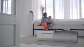 Madre feliz y pequeño hijo que leen un libro por la mañana junto en la sala de estar en casa concepto de la actividad de la famil almacen de metraje de vídeo