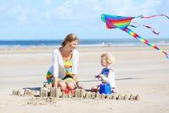 Madre feliz y pequeño niño que juegan en la playa fotos de archivo