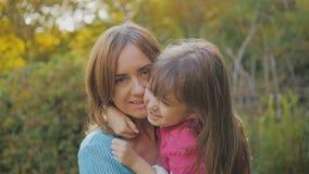 madre feliz y risa y giro de la hija el bebé abraza a la mamá por el cuello y ríe Parque del otoño A cámara lenta almacen de video