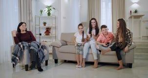 Madre feliz y sonriente concentrada con sus ni?os que pasan el tiempo junto mientras que juegan en un videojuego tienen a almacen de metraje de vídeo