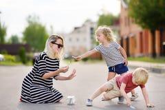 Madre feliz y su dibujo del niño pequeño y de la muchacha con tiza coloreada en el asfalto fotos de archivo