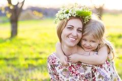 Madre feliz y su pequeña hija en un jardín floreciente Foto de archivo