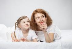 Madre feliz y su pequeña hija que juegan en la cama fotos de archivo libres de regalías