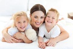 Madre feliz y sus niños que mienten en una cama Imágenes de archivo libres de regalías