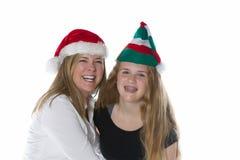 Madre feliz y sus sombreros del día de fiesta de la hija que llevan Imagenes de archivo