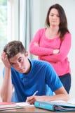 Madre frustrada que mira al hijo adolescente el hacer de la preparación Imágenes de archivo libres de regalías