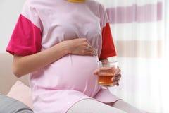 Madre futura con el vidrio de alcohol en casa, primer foto de archivo