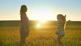 Madre giovane e piccola figlia con capelli biondi lunghi che saltano in mezzo al giacimento ed a sorridere di grano, bei archivi video