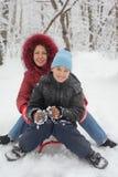 Madre, giro del figlio sulla slitta Fotografia Stock