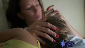 Madre graziosa che lenisce e che abbraccia gridando neonata La bella giovane madre calma gridare la figlia, a casa archivi video