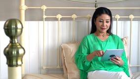 Madre hermosa asiática e hija bastante adolescente con la tableta Fotografía de archivo