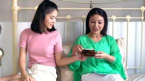 Madre hermosa asiática e hija bastante adolescente con la tableta Imagenes de archivo
