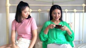 Madre hermosa asiática e hija bastante adolescente con la tableta Fotos de archivo