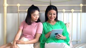 Madre hermosa asiática e hija bastante adolescente con la tableta Fotos de archivo libres de regalías