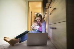 Madre hermosa con el hijo en los brazos, trabajando en el ordenador portátil Foto de archivo