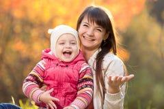 Madre hermosa con el niño al aire libre en otoño Fotos de archivo