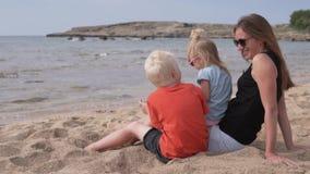 Madre hermosa con los niños que se sientan en la playa y que miran el mar almacen de metraje de vídeo