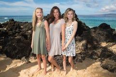 Madre hermosa con sus dos hijas en una playa fotografía de archivo libre de regalías