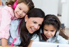 Madre hermosa con sus hijas que escuchan la música en casa fotos de archivo