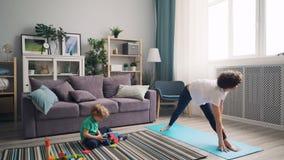 Madre hermosa de la muchacha que hace yoga cuando niño que juega con los juguetes en piso por mañana metrajes