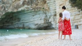 Madre hermosa e hija en la playa que disfrutan de vacaciones de verano almacen de metraje de vídeo