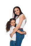 Madre hermosa e hija felices que se colocan de abarcamiento y sonrientes en la cámara Fotografía de archivo