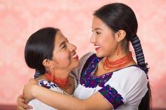 Madre hermosa e hija hispánicas que llevan la ropa andina tradicional, abrazando mientras que presenta feliz junto Imagenes de archivo