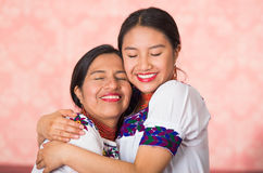 Madre hermosa e hija hispánicas que llevan la ropa andina tradicional, abrazando mientras que presenta feliz junto Imágenes de archivo libres de regalías