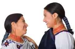 Madre hermosa e hija hispánicas que llevan la ropa andina tradicional, abrazando mientras que presenta feliz junto Fotografía de archivo