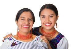 Madre hermosa e hija hispánicas que llevan la ropa andina tradicional, abrazando mientras que presenta feliz junto Fotos de archivo