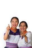 Madre hermosa e hija hispánicas que llevan la ropa andina tradicional, abrazando mientras que presenta feliz junto Foto de archivo
