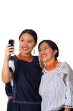 Madre hermosa e hija hispánicas que llevan la ropa andina tradicional, abrazando mientras que presenta feliz junto Imagen de archivo