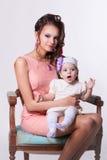 Madre hermosa en un vestido rosado y peinado con su hija en Foto de archivo