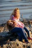 Madre hermosa feliz y su hija que se divierten en la playa rocosa en la puesta del sol Fotografía de archivo