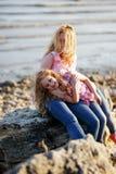 Madre hermosa feliz y su hija que se divierten en la playa rocosa en la puesta del sol Fotos de archivo libres de regalías