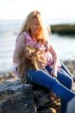Madre hermosa feliz y su hija que se divierten en la playa rocosa en la puesta del sol Fotos de archivo