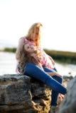 Madre hermosa feliz y su hija que se divierten en la playa rocosa en la puesta del sol Imagenes de archivo