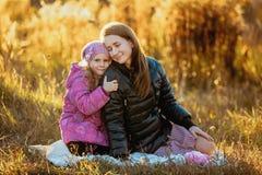 Madre hermosa joven con su hija en un paseo en un día soleado del otoño Se están sentando en una tela escocesa en la hierba cerca imagenes de archivo