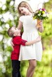 Madre hermosa joven con su hijo Una mujer y un bebé con un ramo, una cesta de flores Concepto de la primavera de vacaciones de fa Foto de archivo