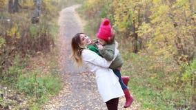 Madre hermosa joven con una pequeña hija que se divierte en el bosque del otoño almacen de metraje de vídeo