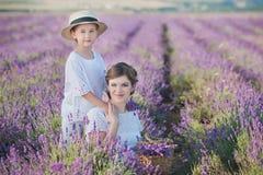 Madre hermosa joven de la señora con la hija preciosa que camina en el campo de la lavanda en un día del fin de semana en vestido imágenes de archivo libres de regalías