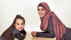 Madre hermosa joven en el hijab con su pequeña hija, mirada en la cámara, familia de risa, concepto de familia feliz, idilio metrajes