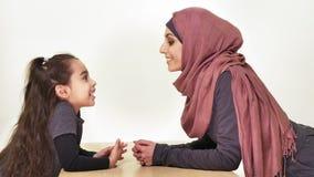 Madre hermosa joven en el hijab con su pequeña hija, mirada en uno a, familia de risa, concepto de familia feliz almacen de metraje de vídeo