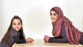 Madre hermosa joven en el hijab con su pequeña hija, mirada en uno a y in camera, familia de risa, feliz metrajes