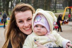 Madre hermosa joven en el patio con un bebé que sonríe y que juega Foto de archivo libre de regalías