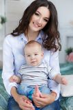 Madre hermosa joven que celebra al hijo del bebé en su revestimiento, sentándose en una cama imagen de archivo