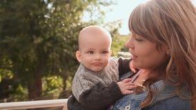 Madre hermosa joven que celebra a un bebé en sus brazos Mime a abrazar y a besar a su hijo en la naturaleza almacen de metraje de vídeo