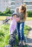 Madre hermosa joven que juega con su hija en el patio en la hierba que se sienta en las ruedas Imagenes de archivo