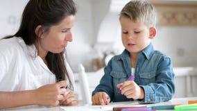 Madre hermosa que ayuda a poca imagen de la pintura del hijo usando rotulador coloreado metrajes