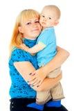 Madre hermosa que celebra a un bebé en sus brazos fotos de archivo